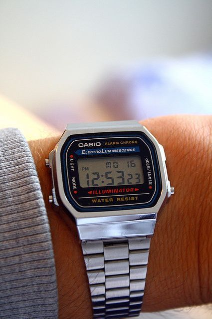 Foto com foco em um relógio no pulso de um homem. O relógio é da marca Casio e tem formato quadrangular, com marcador de horas em numeral.