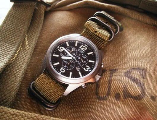 Foto de relógio acima de uma bolsa. Além de marcar as horas, ele conta com funcionalidades e ainda tem uma pulseira forte com diversos prendedores.