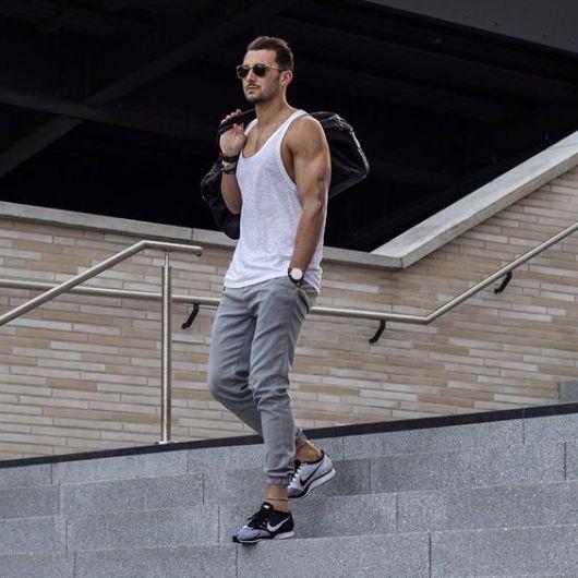 Homem descendo uma escada. Ele veste uma camiseta regada cavada, calça moletom jogger, tênis da Nike, óculos escuros e um relógio prata arredondado.