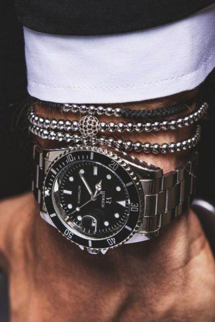 Foto do pulso de um homem com parte de um traje social acompanhado por pulseiras e um relógio prata repleto de detalhes.