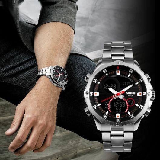Montagem que contém a foto do braço de um homem recostado em sua perna. Ao lado, vemos em detalhe o relógio que ele está usando, que consiste em um modelo que marca a hora em numerais e ponteiros, além de outras funcionalidades no painel interno.