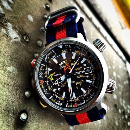 Foto de um relógio repousando em uma superfície metálica. Seu aro é prateado e arredondado, com o interior repleto que funcionalidade esportivas que vão muito além de marcar a hora. A pulseira é colorida e tem prendedores fortes.