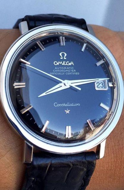 Foto de um relógio da marca Omega arredondado com pulseira de couro e pulseira prata.