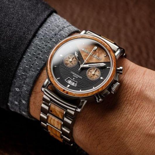 Foto do pulso de um homem vestindo trajes formais. O relógio possui três botões laterais e seu aro e pulseira contêm detalhes de madeira mesclados ao prata.