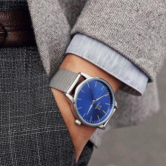 Foto do pulso de um homem com a mão no bolso vestindo um traje social. Ele usa um relógio arredondado prata com poucos botões ou detalhes. O destaque fica na pulseira que tem uma textura em relevo.