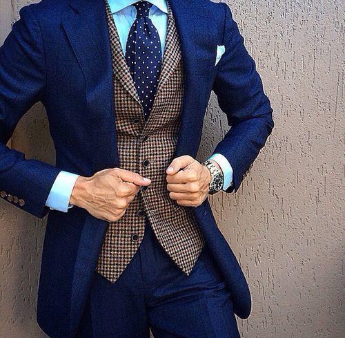 Foto do tronco de um homem vestindo terno e grava. Ele está segurando seu terno com as duas mãos e uma delas tem um relógio prata bem detalhado.