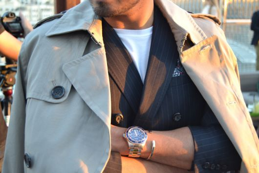 Foto do tronco de um homem com trajes formais de braços cruzados. Em um pulso ele usa um relógio prata iluminado pelo sol acompanhado de uma pulseira da mesma cor.