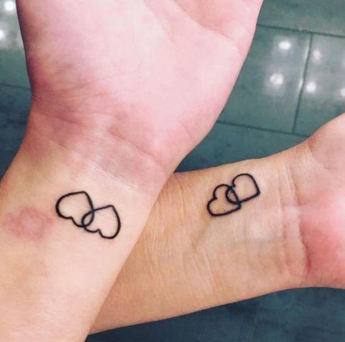 tatuagem de coração no pulso com dois corações