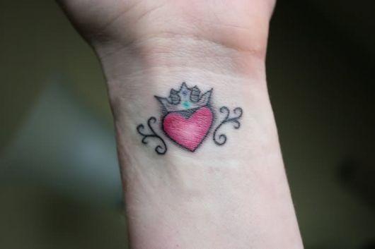 tatuagem de coração no pulso com coroa