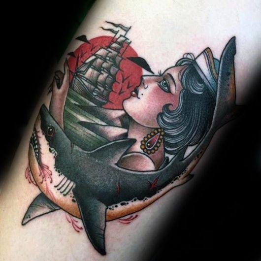 Tatuagem no estilo tradicional de um tubarão com sangue saindo de sua boca e cicatrizes em seu corpo. Acima dele há uma mulher de perfil e uma caravela com o sol vermelho ao fundo.