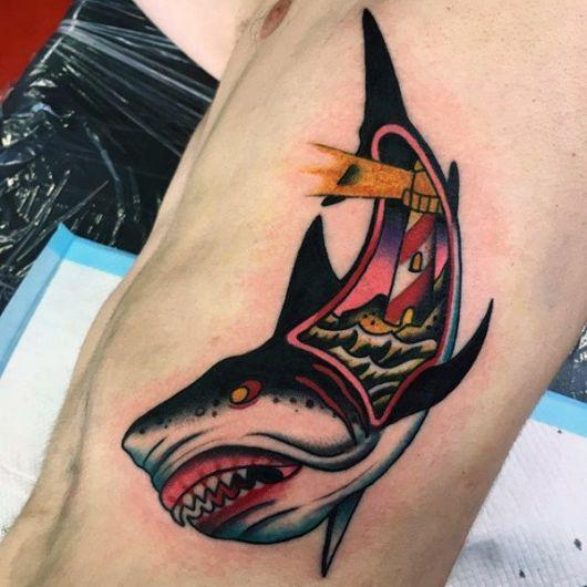 Tatuagem na costela seguindo o estilo Old School com um tubarão agressivo e uma abertura no interior de seu corpo onde há um farol em águas agitadas.