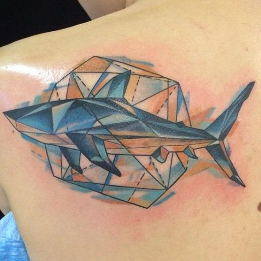 Tatuagem na lateral das costas com um tubarão feito a partir de formas geométricas e um grande hexágono atrás dele.