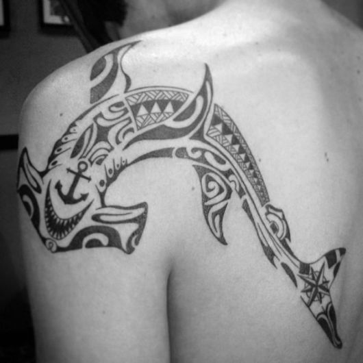 Tatuagem na lateral das costas que vai até parte do ombro com o desenho de um tubarão martelo feito no estilo maori.