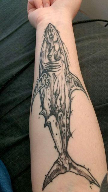 Tatuagem no antebraço de um tubarão visto de perfil. Ele é formado por estranhos rabiscos que dão a ele uma aparência robótica.