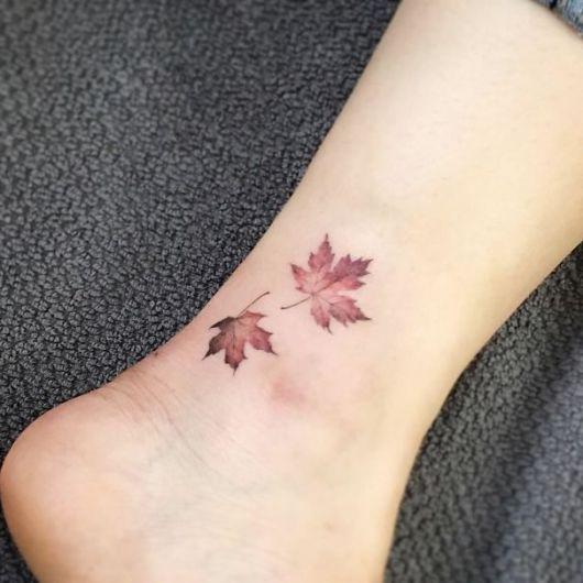 Modelo com tatuagem de folhas secas.