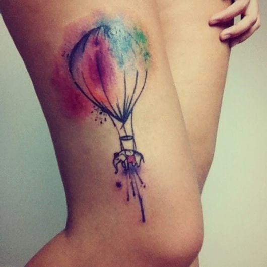 Mulher com tatuagem na perna de balão colorida em tons de rosa,azul e laranja.