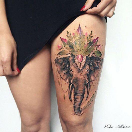 Tatuagem aquarela de elefante na coxa esquerda em tons de verde e preto e branco.