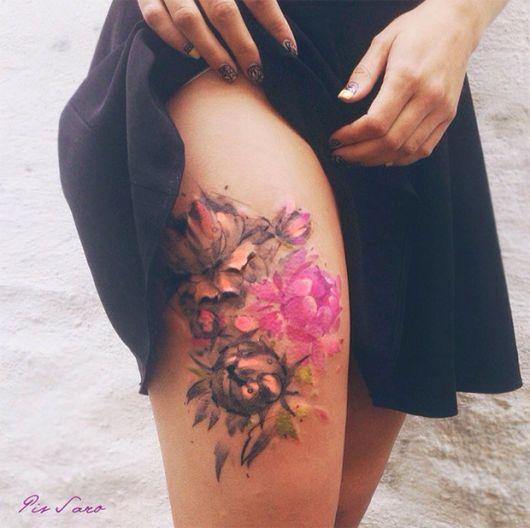 Modelo usa tatuagem na coxa de flor em cores aquarela em tons de rosa, verde e amarelo.