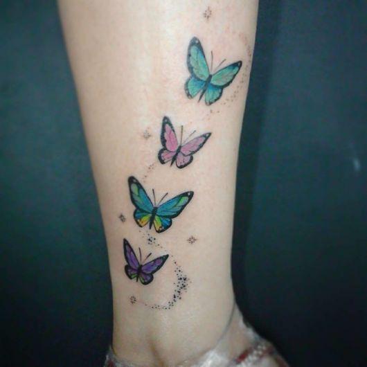 Mulher com tatuagem de 4 borboleta pequenas nas cores azul com amarelo, verde, rosa e roxo.