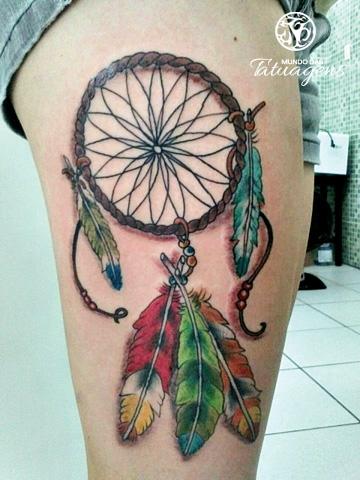 Tatuagem na coxa com penas na cor verde, vermelho e azul.