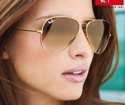 Modelo usa óculos ray ban dourado com lentes marrom.