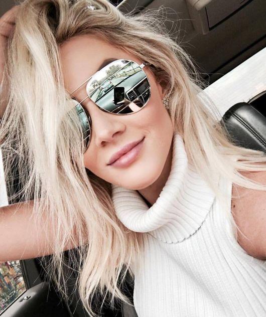 Modelo usa blusa de gola rolè branca e óculos de sol prata ray ban.