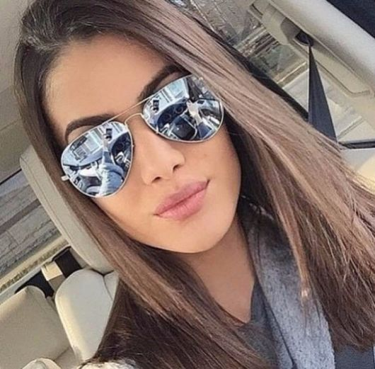 Modelo usa óculos de sol lente espelhada azul.