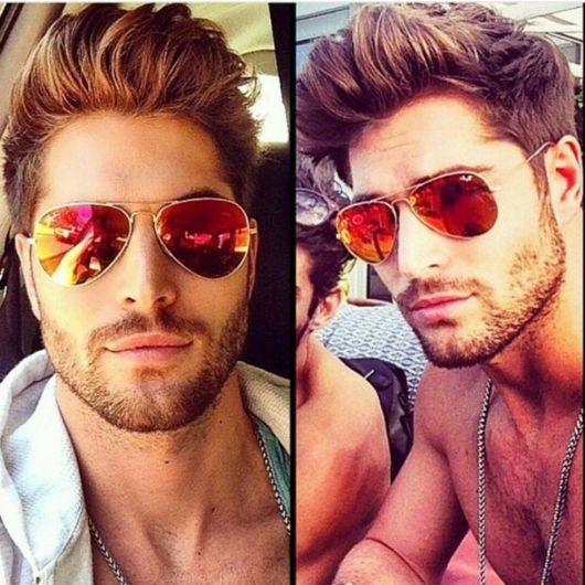 Modelo usa óculos espelhado vermelho.