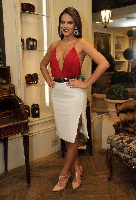 Bruna Marquezine com body transpassado vermelho e saia branca.