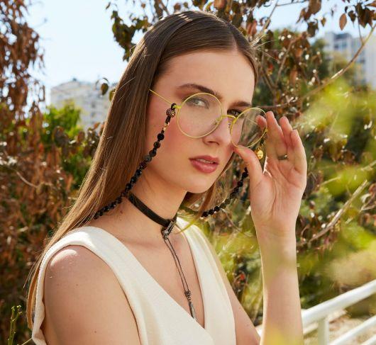 Modelo usa regata branca, óculos de grau e corrente pingente preta.