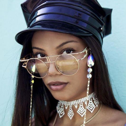 Modelo usa corrente delicada com pedras e óculos de lentes transparentes.
