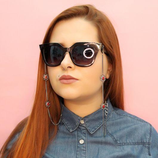 Modelo usa cmisa gola polo e corrente pingente de óculos delicada em metal.
