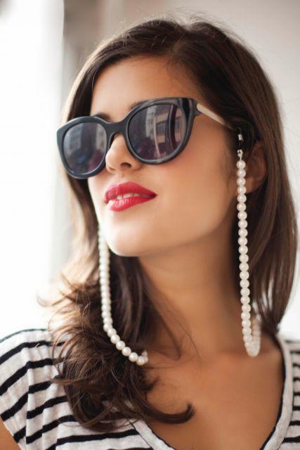 Modelo usa óculos escuros preto com corrente de pérolas.