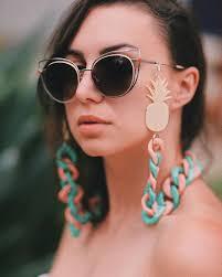 Modelo usa óculos escuros com corrente nas cores rosa e azul água.