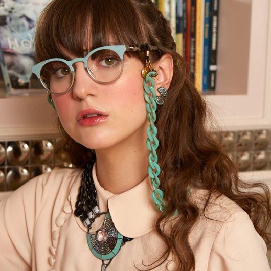 Modelo usa camisetinha polo rosê, óculos de grau com corrente verde.