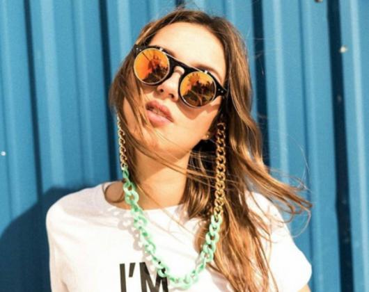 Modelo usa camiseta branca estampada de letras, óculos espelhados e corrente dourada com verde.