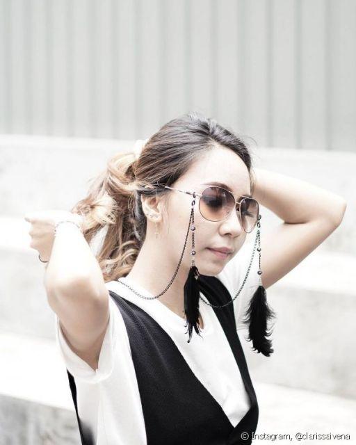 Modelo veste blusa preta e branca, óculos redondo e corrente de metal com penas.