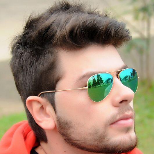 Modelo usa óculos de sol ray ban espelhado na cor verde.