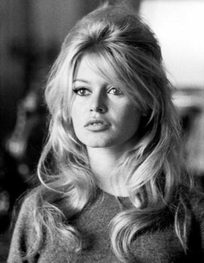 Atriz Brigitte Bardot usa cabelo longo ondulado com penteado moicano semi preso.