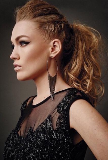 Modelo usa blusa preta transparente, brincos de metal e rabo de cavalo com trança e moicano feminino.