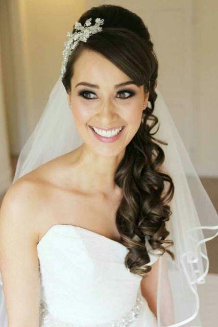 Modelo usa vestido de noiva com penteado moicano lateral e franja.