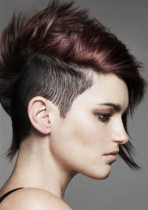 Modelo usa cabelo cor caju com moicano curto raspado nas laterais.