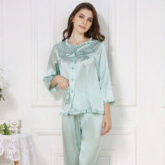 Modelo usa pijama longo de seda azul bebê.
