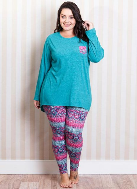 Modelo usa calça justa de pijama colorida e blusa azul manga longa de pijama.