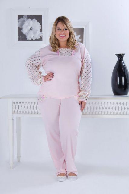 Modelo usa pijama manga longa rosa clarinho.