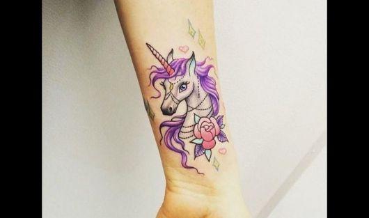 Tatuagem de unicórnio colorida nas cores de roso, rosa e amarelo.