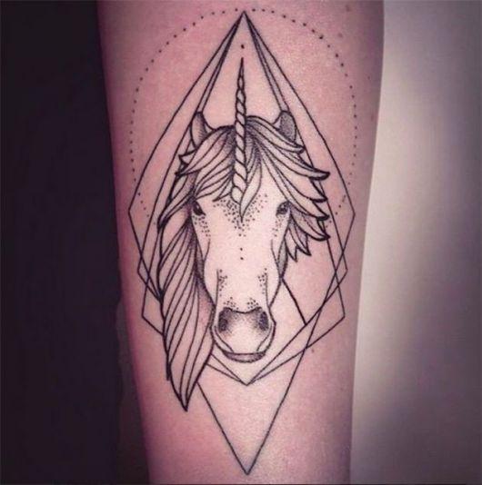 Tatuagem de unicórnio preta com triangulo ao fundo.