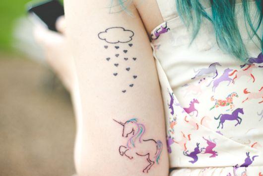 Tatuagem de unicórnio pequena com nuvem de corações.