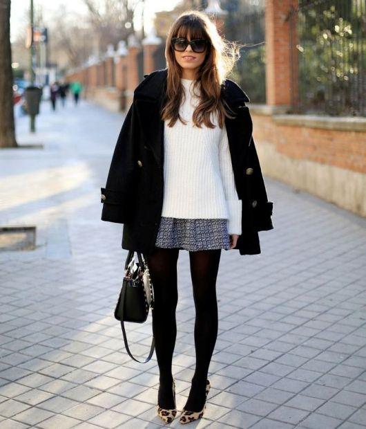 Modelo usa blusa de lã branca, saia curta, meia preta, sapato e bolsa preta.