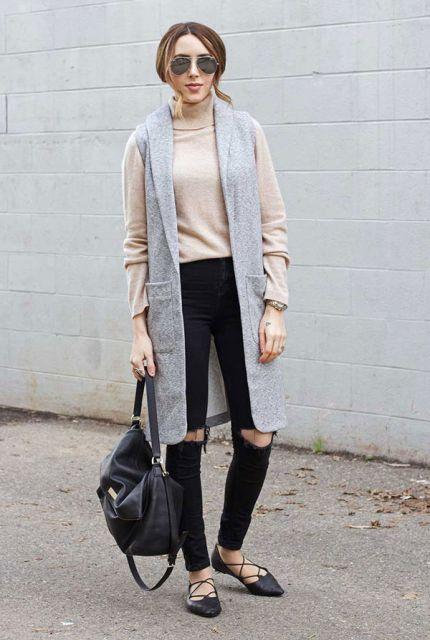 Modelo veste maxi colete cinza, blusa de lã gola alta bege, calça rasgada no joelho preta e sapatilha preta.